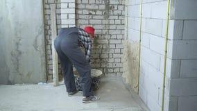 Homem no desgaste do trabalho e no tampão vermelho que emplastra a parede ventilada do bloco de cimento filme