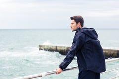 Homem no desgaste dos esportes que está o mar próximo fotos de stock