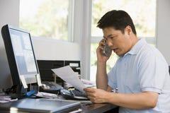 Homem no escritório home com computador e documento imagem de stock royalty free