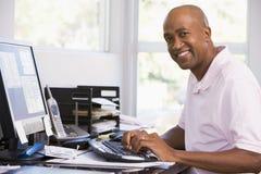 Homem no escritório home usando o computador e o sorriso fotos de stock royalty free