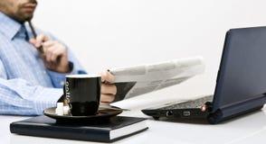Homem no escritório, lendo o jornal fotografia de stock