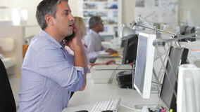 Homem no escritório na mesa usando o telefone celular e o computador video estoque