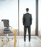 Homem no escritório que olha para fora a janela Imagens de Stock Royalty Free
