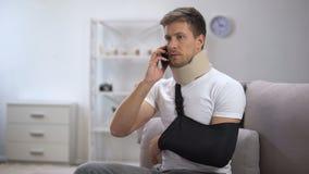Homem no estilingue do braço e no colar cervical da espuma que fala no telefone celular, virada com notícia video estoque