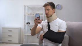 Homem no estilingue do braço e para espumar desdobramento cervical no smartphone, período do colar da reabilitação vídeos de arquivo