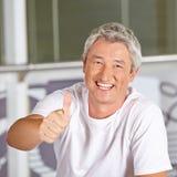 Homem no fitness center que mantém os polegares Fotografia de Stock Royalty Free