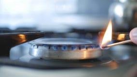 Homem no fogo de abertura da cozinha com fósforos no fogão de gás fotos de stock