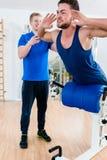 Homem no gym no banco do exercício que obtém o auxílio pelo instrutor pessoal imagens de stock