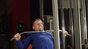 Homem no gym, mãos de formação do tríceps O homem levanta o peso pesado no gym Homem forte dos esportes Treinamentos com um pesad video estoque