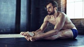 Homem no gym que faz esticando exercícios foto de stock