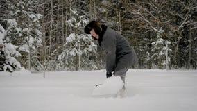 Homem no inverno depois que a pá da queda de neve limpa o trajeto da neve no fundo da floresta vídeos de arquivo