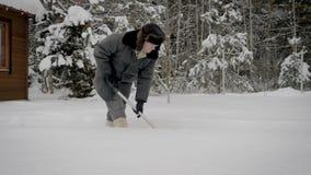 Homem no inverno depois que uma queda de neve limpa a pá a passagem à casa de madeira filme