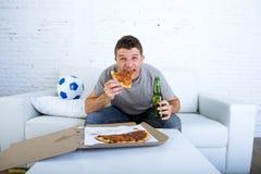 Homem no jogo de futebol de observação do esforço na televisão que come a cerveja bebendo da pizza que olha entusiasmado e ansios Fotografia de Stock
