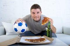 Homem no jogo de futebol de observação do esforço na televisão que come a cerveja bebendo da pizza que olha entusiasmado e ansios Foto de Stock