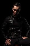 Homem no levantamento preto do casaco de cabedal assentado no estúdio escuro foto de stock