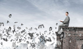 Homem no livro de leitura da borda do telhado e símbolos que voam ao redor Foto de Stock Royalty Free