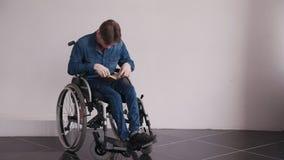 Homem no livro de leitura da cadeira de rodas em casa video estoque