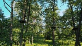 Homem no parque da corda da aventura que faz exercícios de escalada no feixe de equilíbrio no verão filme