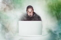 Homem no portátil com luzes e fumo coloridos Foto de Stock Royalty Free