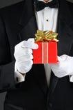 Homem no presente do Natal da terra arrendada do smoking fotos de stock