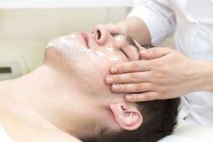 Homem no procedimento do cosmético da máscara foto de stock
