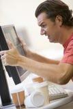 Homem no quarto de computador que agarra seu computador Imagem de Stock Royalty Free
