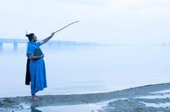 Homem no quimono azul perto do rio que aponta com a vara de madeira no céu fotos de stock