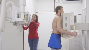 Homem no raio X da preparação do procedimento e da enfermeira do roentgen dos pulmões para examinar filme