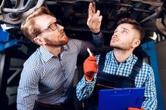 Homem no resultado do trabalho de um mecânico O cliente avalia o reparo do carro por um mecânico Imagens de Stock Royalty Free