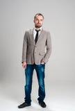 Homem no revestimento cinzento e na calças de ganga que guardam sua mão em olá! Fotos de Stock