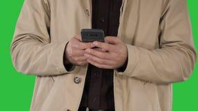 Homem no revestimento de trincheira usando o telefone esperto móvel em uma tela verde, chave do croma vídeos de arquivo