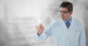 Homem no revestimento e nos óculos de proteção do laboratório que apontam no gráfico branco e alargamento contra o fundo cinzento Fotos de Stock