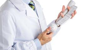 Homem no revestimento médico que guarda a ampola da cópia 3d, lanterna elétrica, phon Foto de Stock