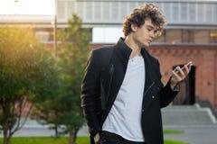 Homem no revestimento preto que olha a tela do telefone celular no fundo urbano da arquitetura da cidade imagens de stock royalty free