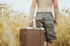 Homem no short que guarda a mala de viagem retro no campo de Fotos de Stock