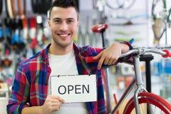 Homem no sinal aberto da terra arrendada da loja da bicicleta Fotos de Stock Royalty Free