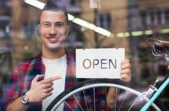 Homem no sinal aberto da terra arrendada da loja da bicicleta Imagem de Stock