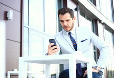 Homem no smartphone - homem de negócio novo que fala no telefone esperto Homem de negócios profissional urbano ocasional que usa  Fotografia de Stock
