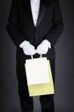Homem no smoking com sacos do presente fotos de stock royalty free
