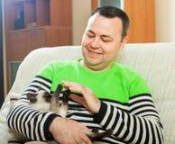 Homem no sofá com animal de estimação pequeno imagens de stock