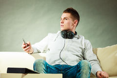 Homem no sofá com fones de ouvido smartphone e tabuleta Imagens de Stock