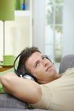 Homem no sofá que escuta o sorriso da música Fotografia de Stock