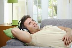 Homem no sofá que escuta o sorriso da música Fotos de Stock Royalty Free