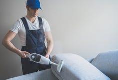 Homem no sofá uniforme da limpeza imagens de stock