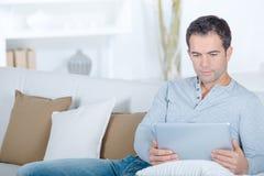 Homem no sofá usando a tabuleta fotografia de stock