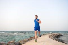 Homem no sportswear que corre no sucesso do futuro da costa de mar corredor bem sucedido Atividade do ver?o Recrea??o do esporte  imagem de stock royalty free