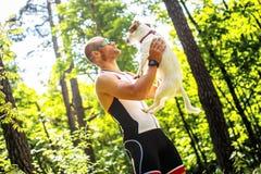 Homem no sportswear que guarda o cão em suas mãos foto de stock royalty free