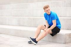 Homem no sportswear que sofre da dor do joelho imagem de stock royalty free