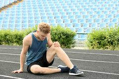 Homem no sportswear que sofre da dor do joelho imagens de stock