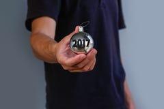 Homem no t-shirt preto que guarda a prata da bola do brinquedo do Natal com insc Imagens de Stock Royalty Free